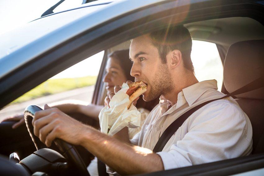 Essen und Trinken im Auto können sich schnell als fahrlässiges Handeln erweisen. (Bild: Martin Novak / Shutterstock.com)