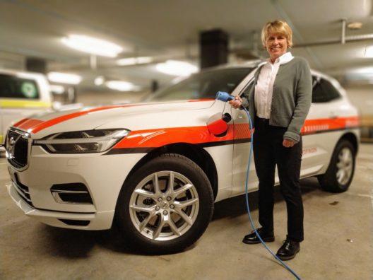 Das neue Hybrid-Fahrzeug kann direkt in der Einstellhalle der Regionalpolizei mit Strom versorgt werden, wie Ressortvorsteherin Christiane Guyer demonstriert.
