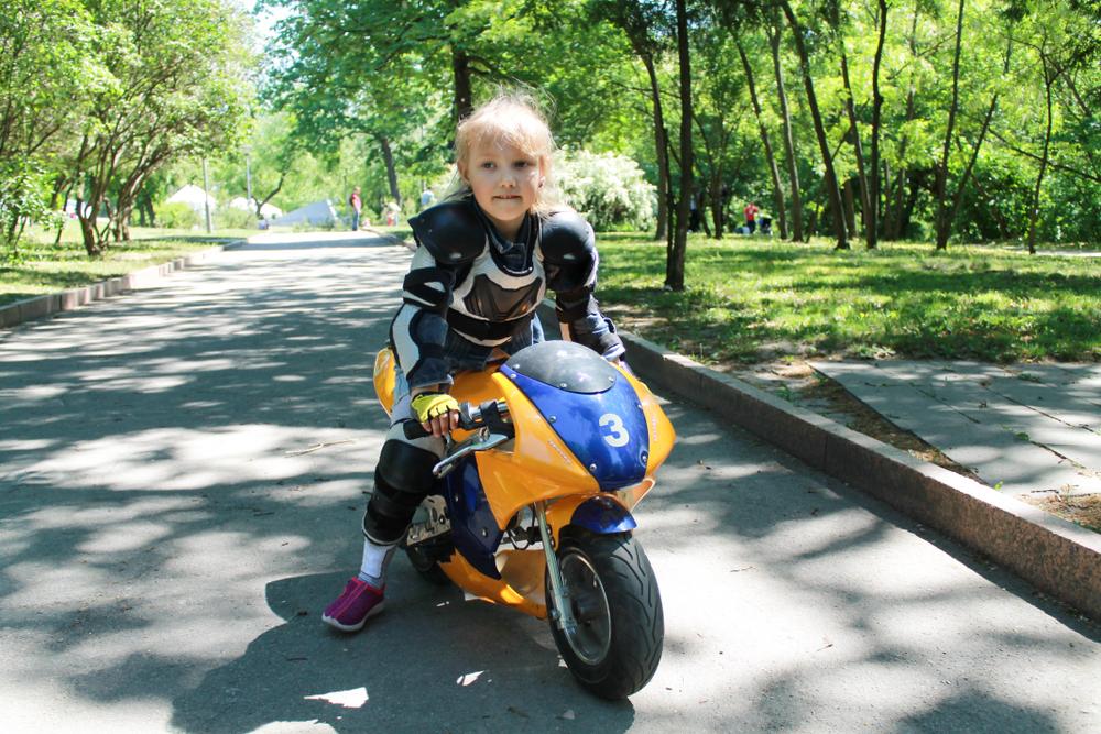 En Mädchen sitzt auf einem Kindermotorrad