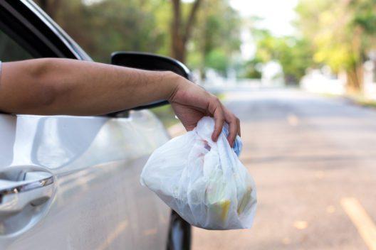 Mann hält aus dem Autofenster einen Müllsack in der Hand