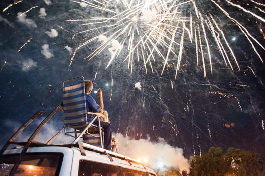 Mann sitzt auf dem Dach eines Autos und betrachtet ein Feuerwerk