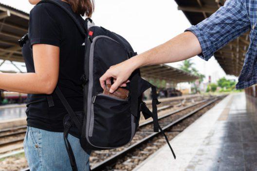 Das Konzept der Vorsicht auf Reisen: Der Dieb hat die Brieftasche einer asiatischen Touristin gestohlen, während sie auf ihre Karte schaute.